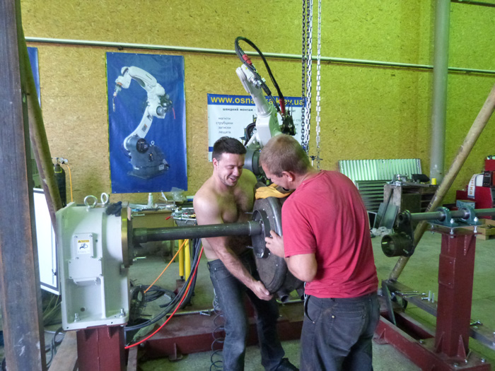 Мужчины за работой - монтаж оснастки робототехнического сварочного комплекса не обходится без грубой мужской силы